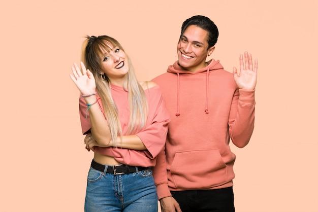 Nel giorno di san valentino giovane coppia salutando con la mano con espressione felice su sfondo rosa