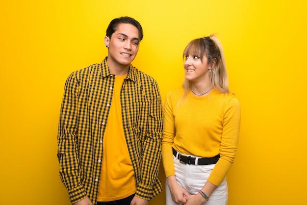 Nel giorno di san valentino giovane coppia su sfondo giallo vivace è un po 'nervoso e spaventato premendo i denti