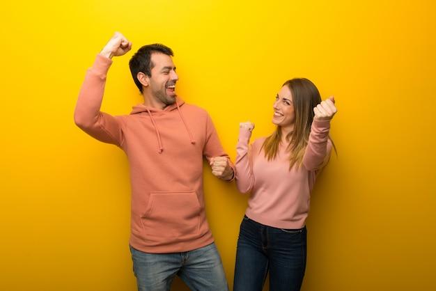 Nel giorno di san valentino gruppo di due persone su sfondo giallo che celebra una vittoria nella posizione di vincitore