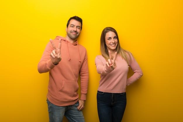 Nel giorno di san valentino gruppo di due persone su sfondo giallo, sorridendo e mostrando il segno della vittoria