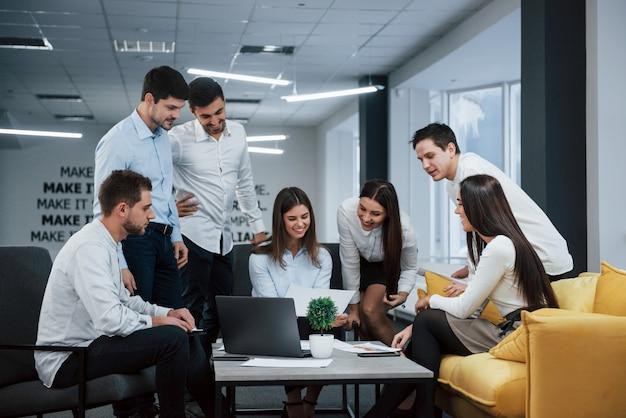 Nel successo. il gruppo di giovani liberi professionisti nell'ufficio ha conversazione e sorridere