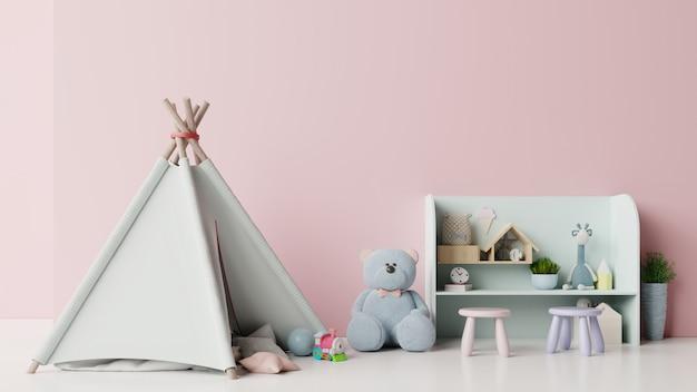 Nella sala giochi per bambini con tenda e tavolo seduto bambola sul muro rosa vuoto.
