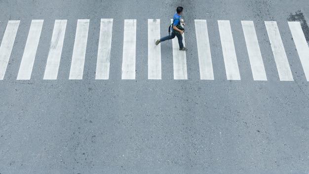 Nella vista laterale dell'uomo cammina veloce attraverso il segno del bivio nella strada della città