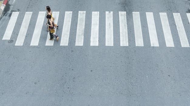 Nella vista laterale delle donne turistiche le persone camminano velocemente attraverso il cartello del bivio nella strada cittadina.