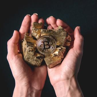 Nelle mani di pezzi d'oro e bitcoin. concetto di estrazione mineraria redditizia