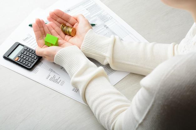 Nelle sue mani una pila di monete e carta sopra la casa sul calcolatore delle dichiarazioni dei redditi