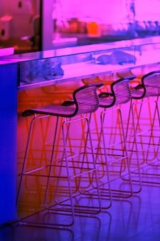 Neon colorato fila vuota di sgabelli in un bar