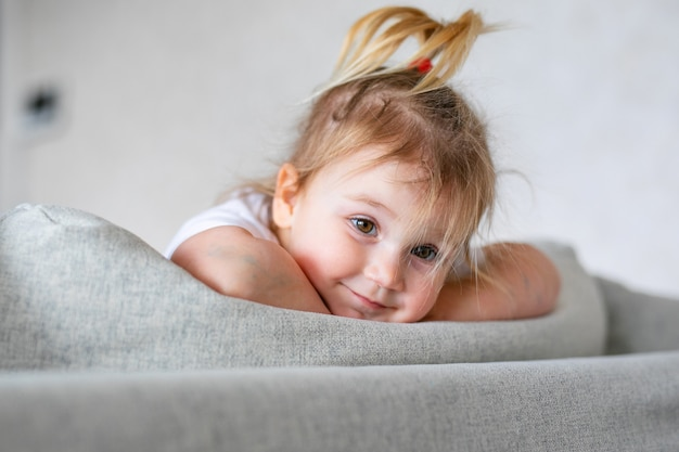 Neonata adorabile in camera da letto soleggiata bianca. neonato che si rilassa su un letto blu. asilo nido per bambini piccoli.