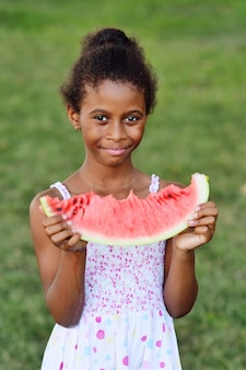 Neonata afroamericana che mangia anguria matura succosa sulla superficie del parco ed erba verde e sorridere