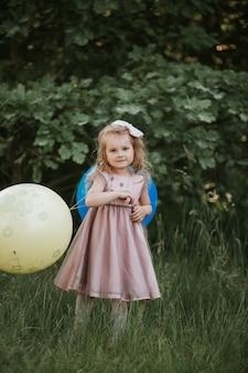 Neonata alla moda 4-5 anni che tiene grande pallone che porta vestito rosa d'avanguardia in prato. giocoso. bambina con un palloncino nel parco. festa di compleanno.