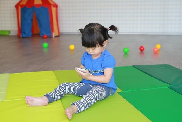 Neonata asiatica che gioca uno smartphone alla stanza del bambino