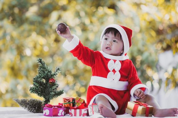 Neonata asiatica sveglia che indossa il vestito di santa con i bei contenitori di regalo sulla celebrazione di natale