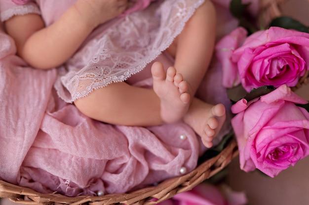 Neonata che dorme nel cestino retrò con fiori di rose da giardino rosa