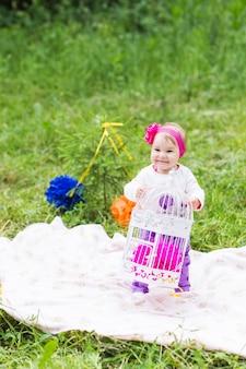 Neonata che gioca sull'erba verde, primo piano di picnic della famiglia.