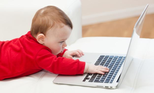 Neonata che per mezzo di un laptop