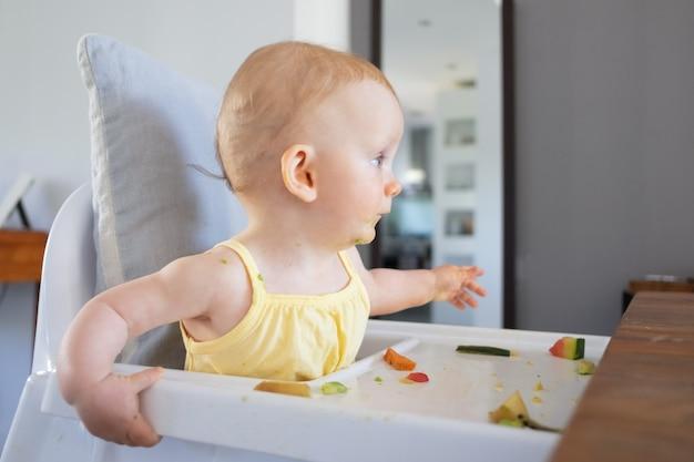 Neonata dai capelli rossi carina con macchie di purea verde sul viso seduto nel seggiolone con cibo disordinato sul vassoio e distogliere lo sguardo. vista laterale. processo di alimentazione o concetto di assistenza all'infanzia