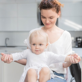 Neonata del primo piano che gioca con la madre a casa