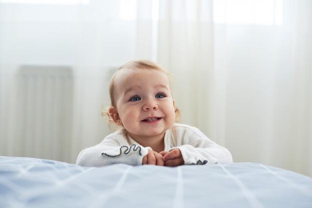 Neonata di un anno che si siede sul pavimento che sorride sul bianco