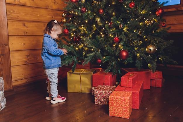 Neonata divertente che decora l'albero di natale