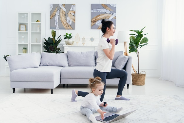 Neonata divertente che gioca con il computer portatile mentre sua mamma sportiva che ha yoga online che si prepara a casa.