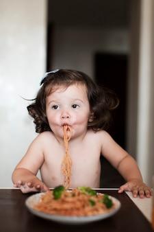 Neonata divertente che mangia spaghetti