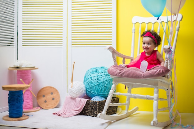 Neonata dolce sorridente felice che si siede sulla poltrona con gli aerostati di compleanno