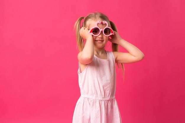 Neonata felice che sorride in occhiali da sole su sfondo rosa