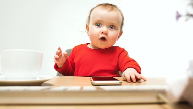 Neonata felice del bambino che si siede con la tastiera del computer o del computer portatile moderno in studio bianco