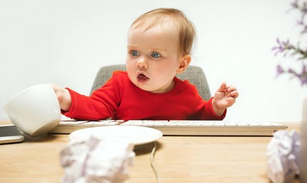 Neonata felice del bambino che si siede con la tazza e la tastiera del computer o del computer portatile moderno isolata sul bianco