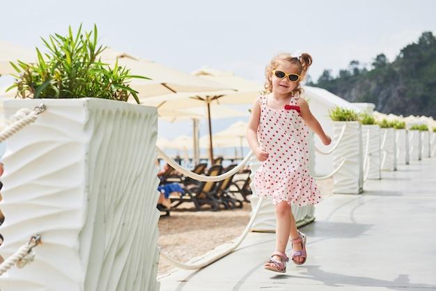Neonata felice in un vestito sulla spiaggia in riva al mare in estate.