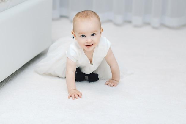 Neonata in vestito bianco su tappeto bianco