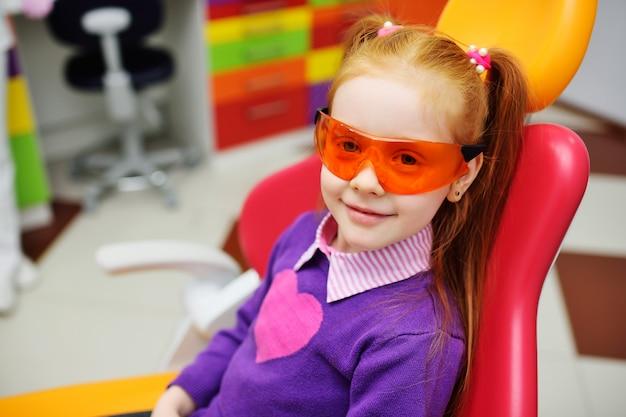 Neonata in vetri dentali che sorride seduta nella sedia dentaria.