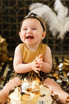 Neonata sorridente che celebra il suo primo compleanno, mangiando torta