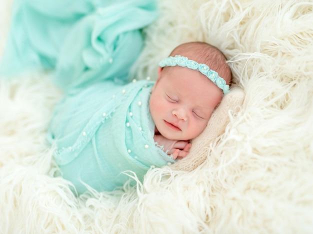 Neonato addormentato in fascia blu