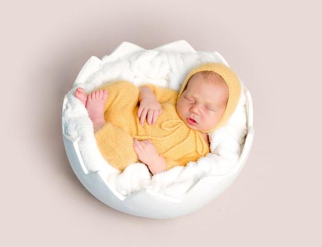 Neonato addormentato rannicchiato sul cestino rotondo