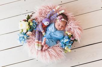 Neonato adorabile con la merce nel carrello di sonno del giocattolo