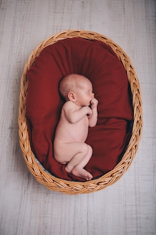 Neonato avvolto in una coperta che dorme in un cestino