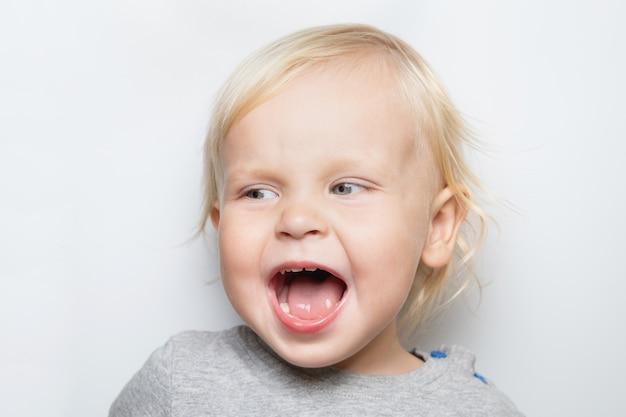 Neonato caucasico di grido in una maglietta grigia sul ritratto bianco del fondo