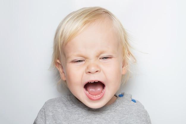 Neonato caucasico esigente di grido in una maglietta grigia su bianco