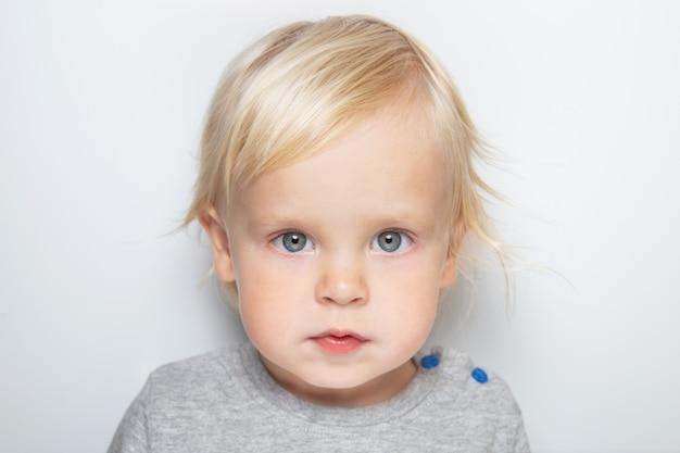 Neonato caucasico sveglio in una maglietta grigia sul ritratto bianco del fondo