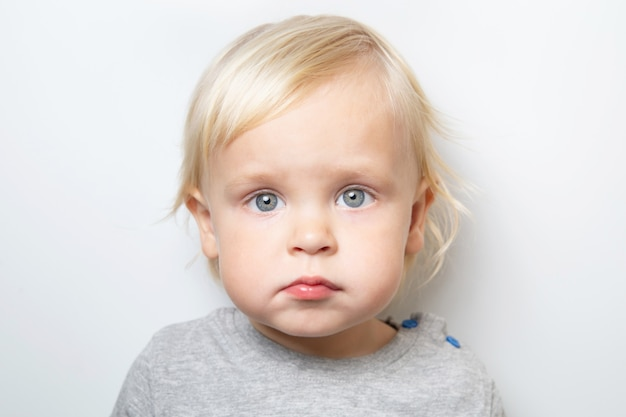 Neonato caucasico triste o timido in una maglietta grigia su bianco