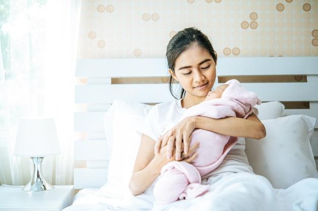 Neonato che dorme nell'abbraccio della madre