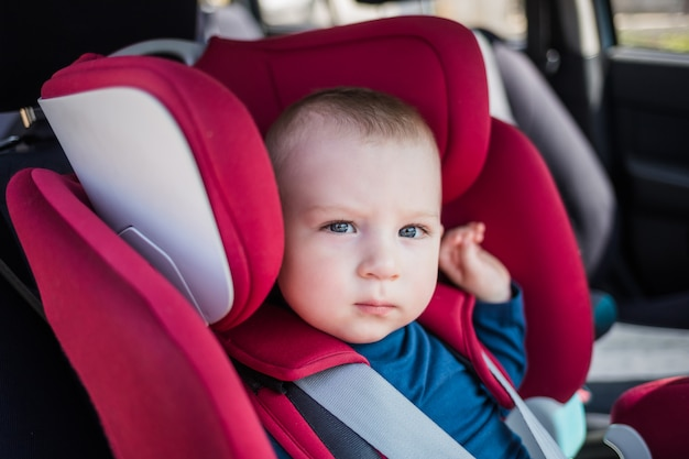 Neonato che si siede in un seggiolino per auto in macchina. un ragazzo carino con un dolcevita blu è seduto su un seggiolino rosso. sicurezza dei movimenti dei bambini.