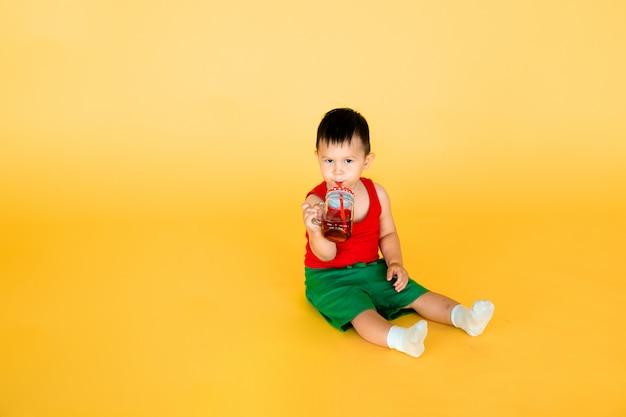 Neonato con bottiglia o brocca di succo o acqua in stile pop art con parete gialla
