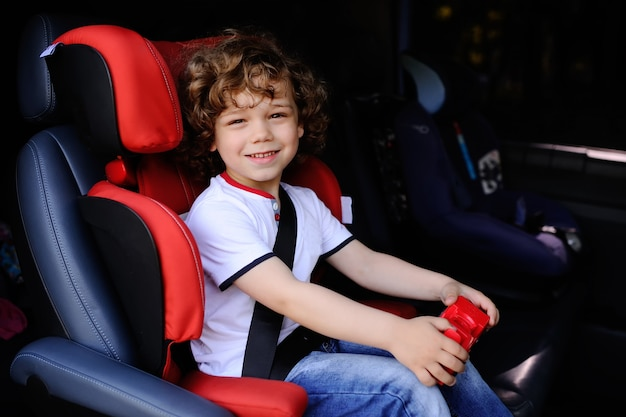 Neonato con capelli ricci che si siedono in un seggiolino auto bambino con auto giocattolo nelle mani