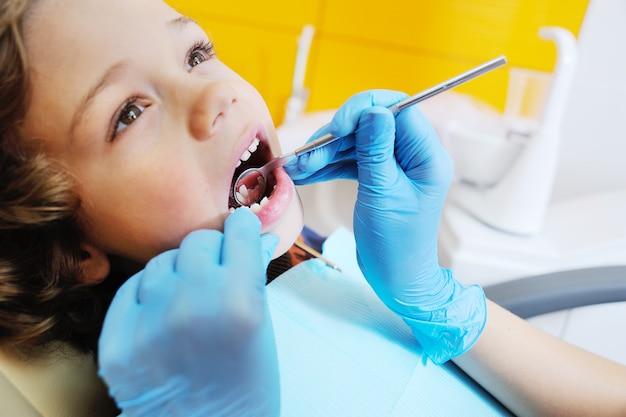 Neonato con capelli rossi ricci in sedia dentale blu. dentista per bambini