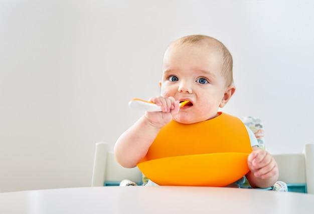 Neonato con il cucchiaio su priorità bassa bianca
