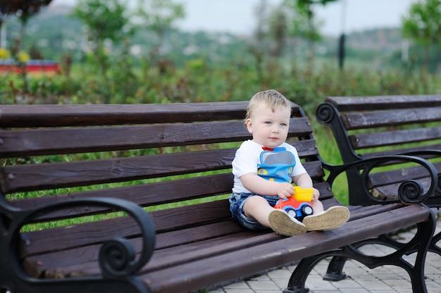 Neonato con l'automobile del giocattolo nelle mani di seduta sulla panchina