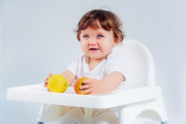 Neonato felice che si siede e che mangia