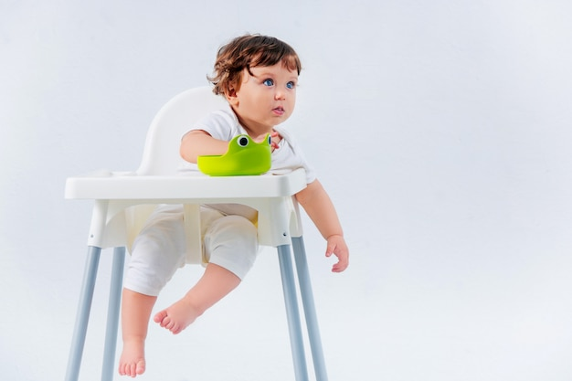 Neonato felice che si siede sulla sedia del bambino